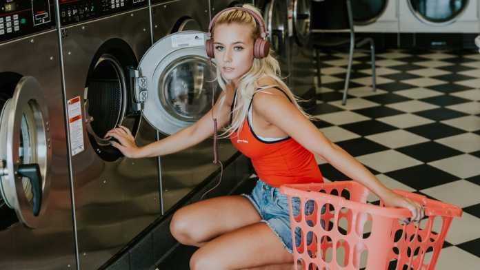 fejhallgatós nő mosógép előtt